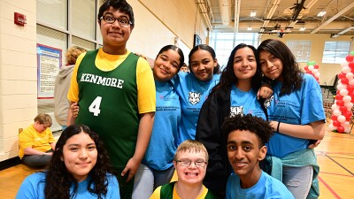 Group of unified athletes stand and kneel together for a group photo. Athletes are wearing yellow and green jerseys and other young athletes have on blue Unified Champion School t-shirts.