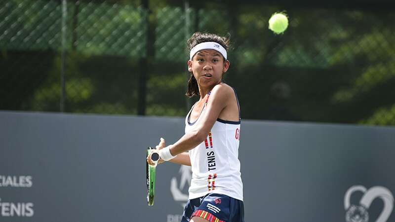 Female athlete playing tennis; taking a swing at the ball during a game.