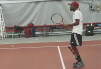 Dionte Foster with his prosthetic leg on  standing on the court with a tennis racket in hand waiting to hit the ball.