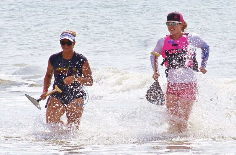 Two women walk out of the ocean smiling.