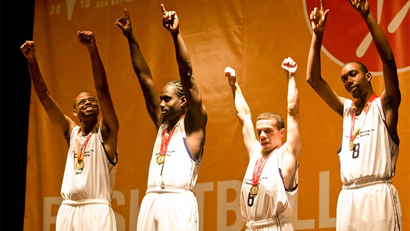 Four basketball players receive medals and all have their arms up in victory.