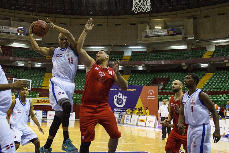 Six player can be seen on the basketball court. One athlete is jumping for a dunk and a player for the opposing team is jumping to defend.