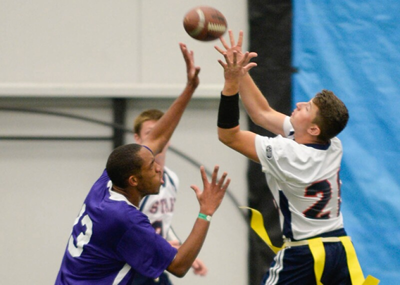 Three young men playing flag football, two of them are reaching for the football.