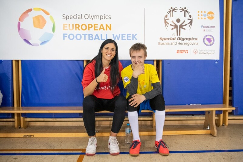 A woman and young man sit on a bench smiling at the camera with their thumbs up in the air. Behind them is a Special Olympics European Football Week banner.