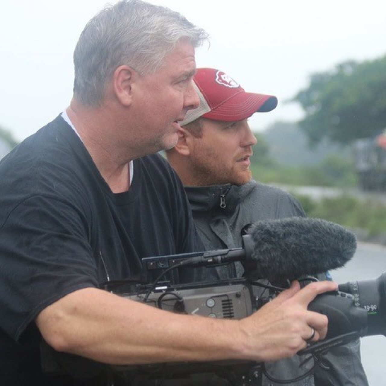 A director and videographer are looking off to the side filming a daytime scene.