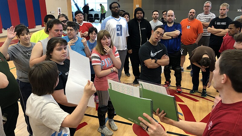 Two representatives show a group of individuals instructions in a gymnasium.