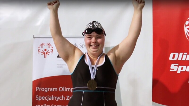 Special Olympics swimming athlete standing with her hands up celebrating wearing a black swim suite, goggles, cap, and her medal; she is standing in front of Special Olympics signage.