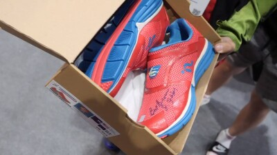 Athlete holding Special Olympics' promotional Fit Feet shoes signed by Bob Beamon.