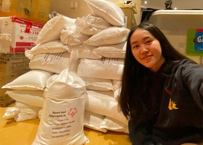 Isabelle sitting in a storage facility next to bags of rice.