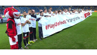 Israeli Hapoel Haifa team, a mascot, and Special Olympics athletes hold up a banner on the pitch before the championship football game starts.