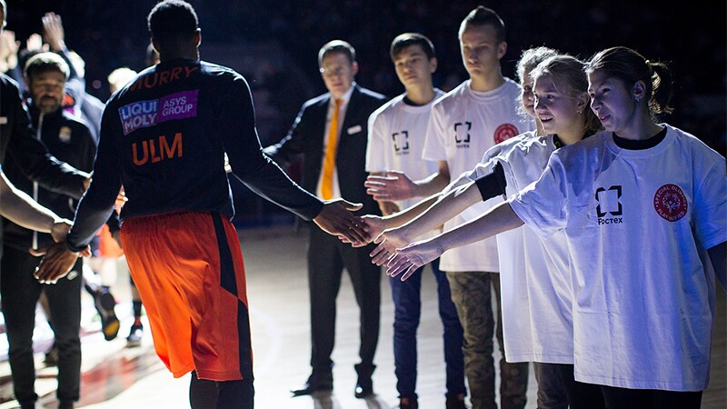 Professional Basketballer ULM giving 5's to people on his left and right as he makes his way to a dimly lit court.
