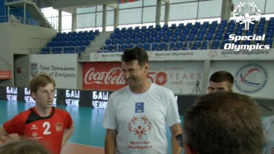 """Vladimir """"Vanja"""" Grbic in a huddle with athletes holding a volleyball."""