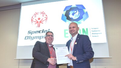 Representatives from Special Olympics and European Football for Development Network shake hands on stage while holding a contract.