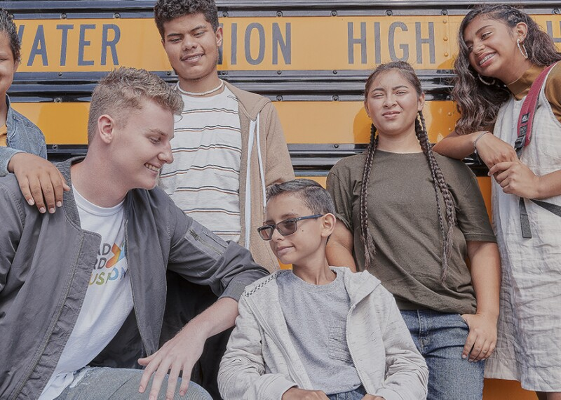 Group of six young adults stand in front of a school bus.