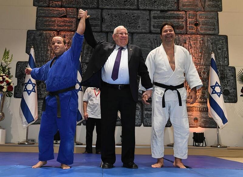Athletes Arik Ze'evi and Levav Barkan pose with Israel's President Reuven Rivlin.