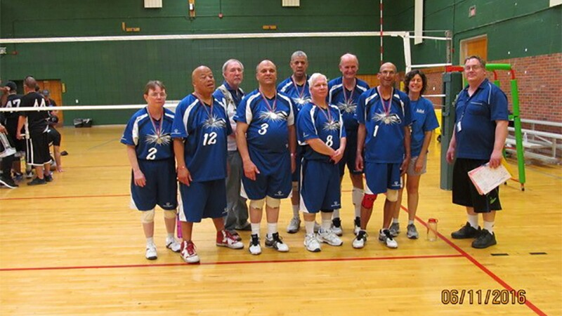 A volleyball team standing on the court and in front of the net for a group photo.
