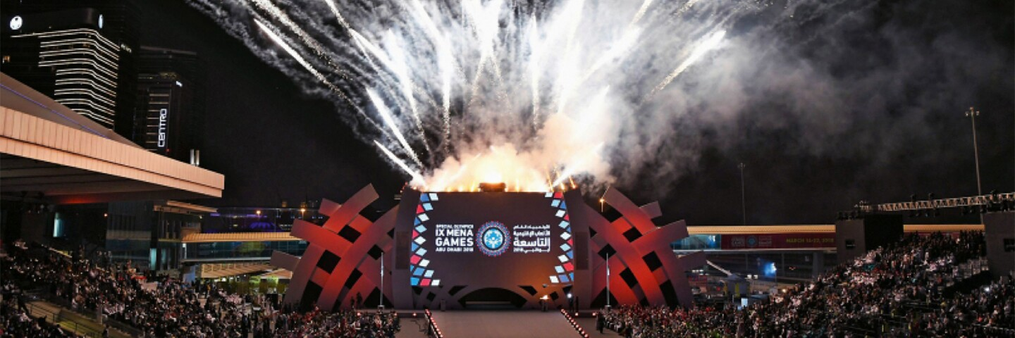A crowd is watching as fireworks going off behind a stage with a backdrop that reads: IX MENA Games.