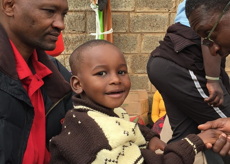 A man holding a small boy, the small boy is looking at the photographer and another man is reaching out and shaking the small boy's hand.