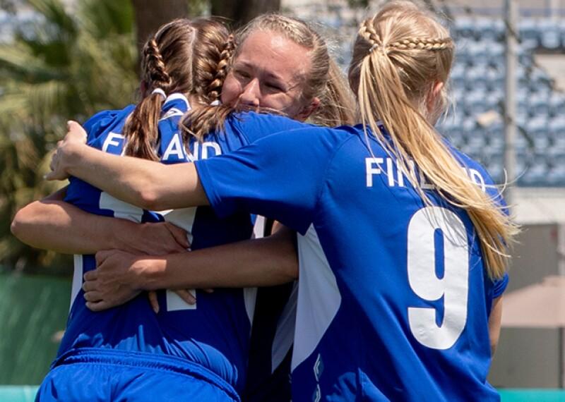 Three girls hug on the football pitch in celebration.