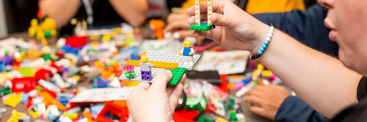 """Group of people sitting around a table working with """"Lego"""" type blocks."""
