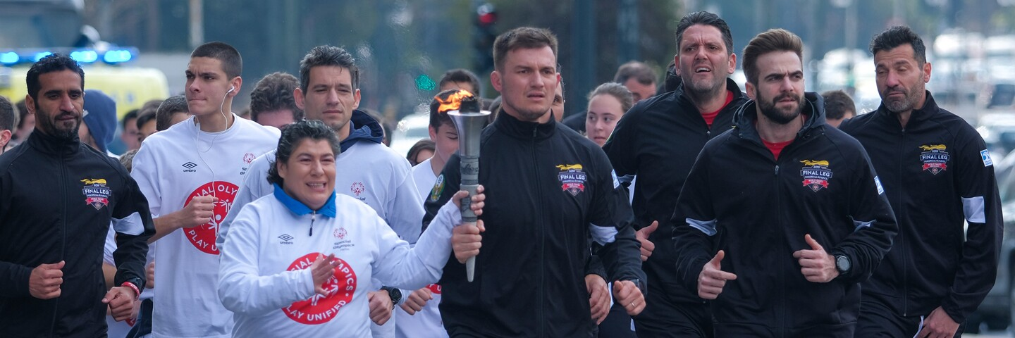 Athletes and Law Enforcement Torch Run officers running together; an athlete is holding the Flame of Hope.
