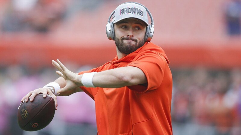 Baker Mayfield warming up; he's in a yellow hoody, a gray Browns hat, with head phones on while throwing a pass with a(n) (American) football.