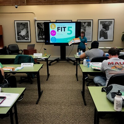 Female Health Messenger teaches about Fit 5 at the front of a classroom.