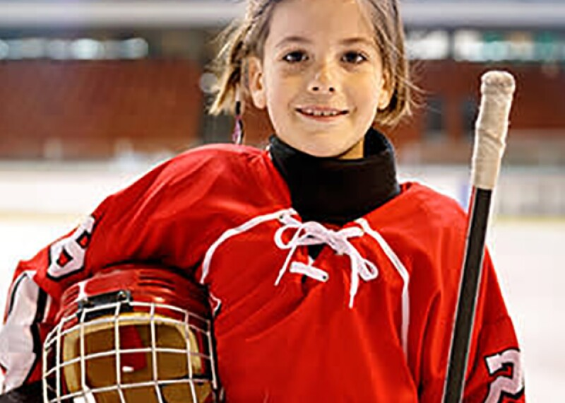 A youth hockey player smiling with her uniform and gear on the ice.