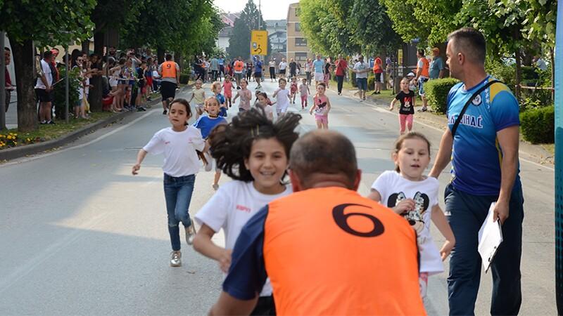 Elementary school kids racing down a street.