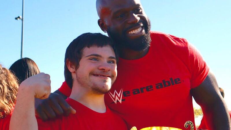 WWE personality and wrestler with his arm around a young athlete holding a golden cup