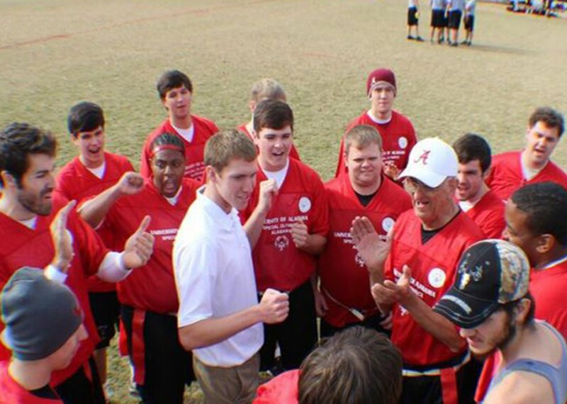 Grou pof students in a huddle around a coach