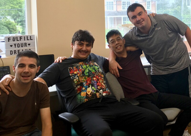 Three young men, Spectrum employees, sitting on chairs and one standing; all four are in a storage room with shelves and supplies. A sign in the background says: Fulfill your dreams.