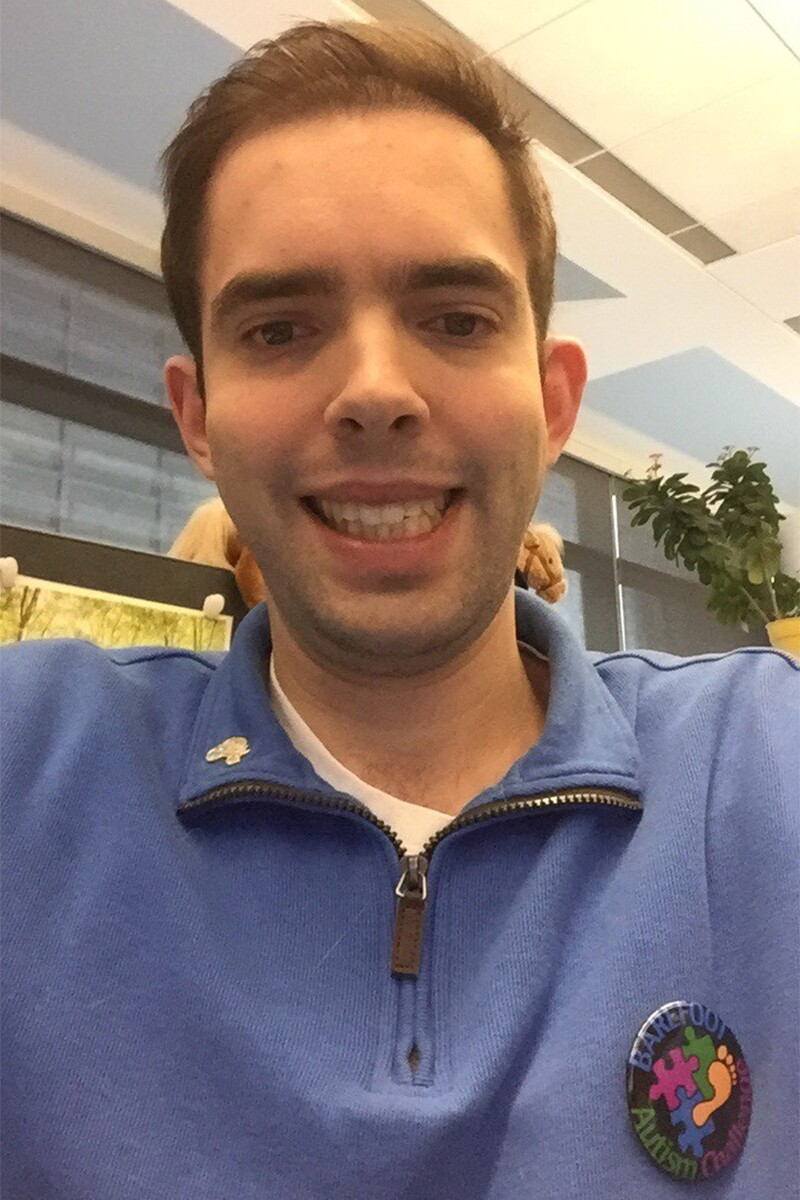 Selfie of Tyler Leech posing with a Barefoot Autism Challenge pin on his chest.