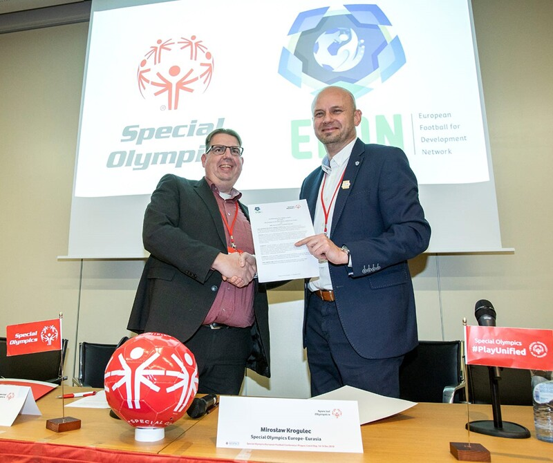 Representatives from Special Olympics and the European Football for Development Network shake hands while on stage holding a contract.