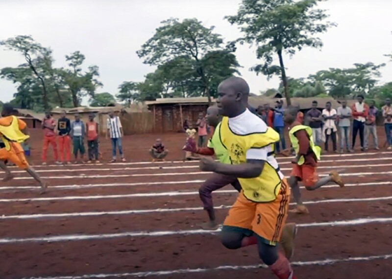 Malachie racing on a track with other athletes.