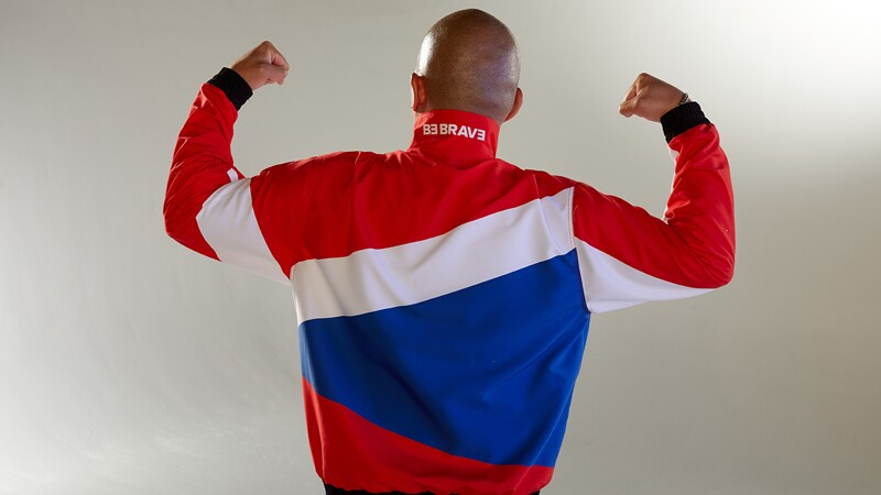 Alfred Ha from the back flexing his biceps showing off his red white and blue jump suit jacket.