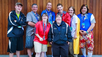 Wal-Mart employees and Special Olympics athletes post for a group photo. Back row consisting of four males on the left, one female then another male on the right. Front row is of two femails. the group is standing inf ront of a wood panel wall. .jpg
