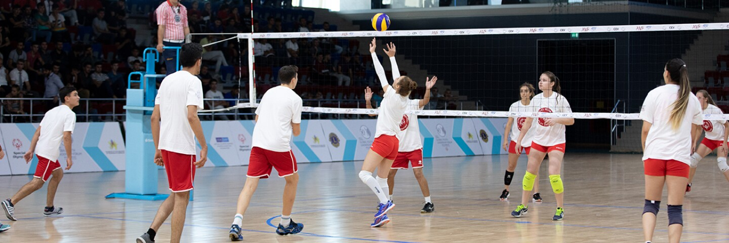 Two unified volleyball teams playing on the court.