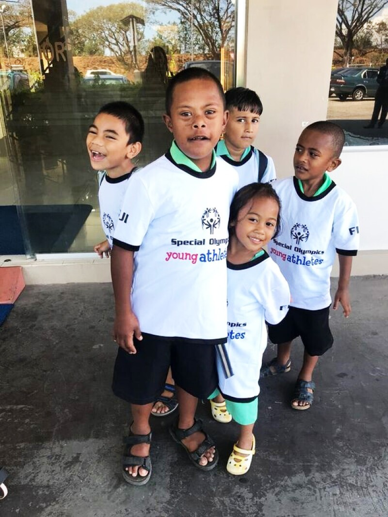 "5 young children part of the Special Olympics program are ""young athletes"" at the recent workshop in Fiji satnding outside in a group, all young athletes have on Special Olympics Young Athletes white t-shirts."