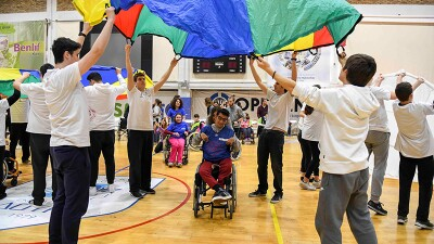 Young adults and athletes playing parachute in a gymnasium.