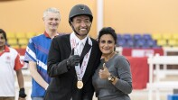 Spencer Roberson in his equestrian gear with a medal around his neck and his arm around a women; both are giving a thumbs up.