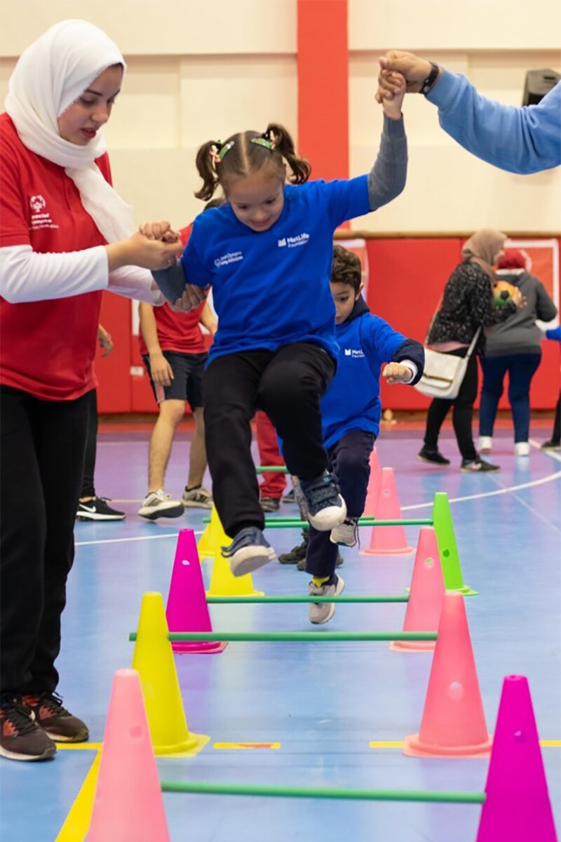 A young girl jumps over a cone obstacle inside a gym, held up by a person on each side. Everyone wears Special Olympics jerseys.
