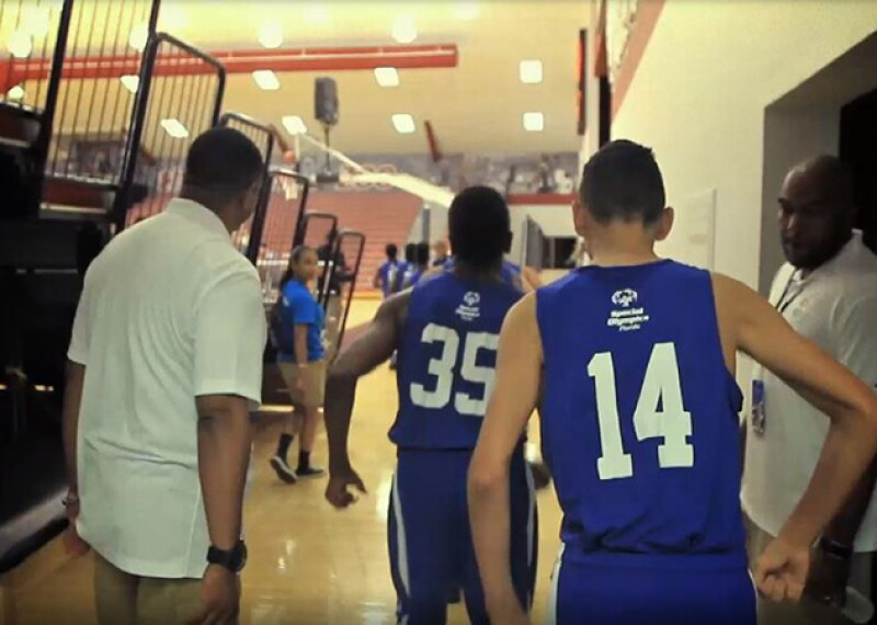 Two athletes walking between coaches and onto the court.