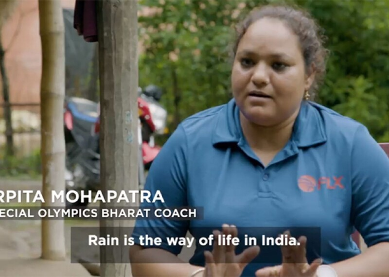 "Arpita Mohapatra sitting in an interview by the film team. She is outside sitting on a chair, she has her hair pulled back and is wearing a blue polo. Text on the screen reads: Arpita Mohapatra, Special Olympics Bharat Coach. ""Rain is the way of life in India."""