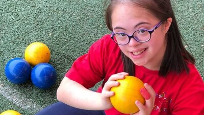 Sara Feldman sitting on a Bocce court holding a bocce ball looking up at the camera and smiling.