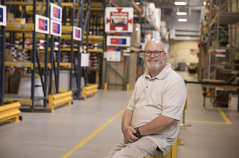 Tommy Fields at work in the Bank of America Support Services marketing fulfillment center. Tom is sitting on a railing in a warehouse facility.