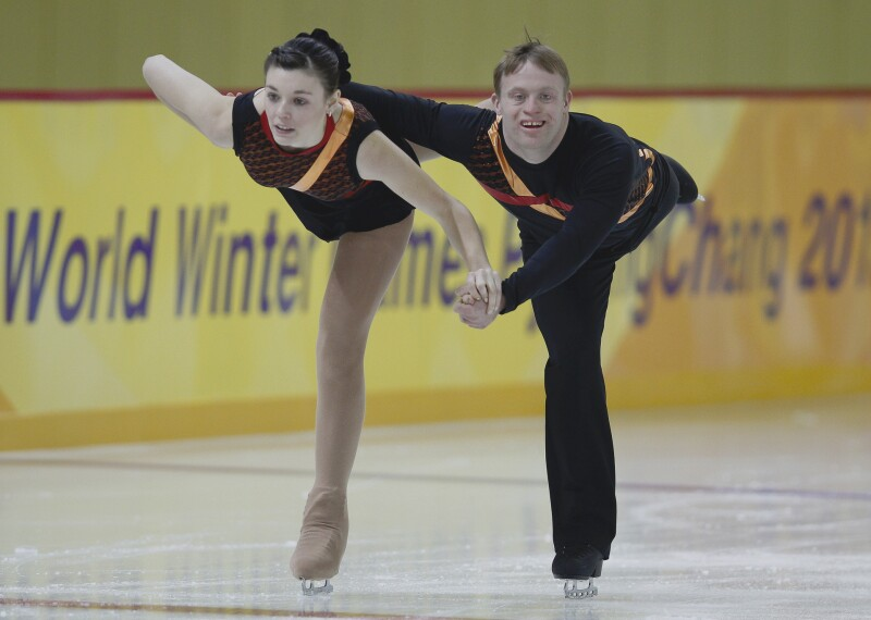 Female and male skating pair performing on the ice.