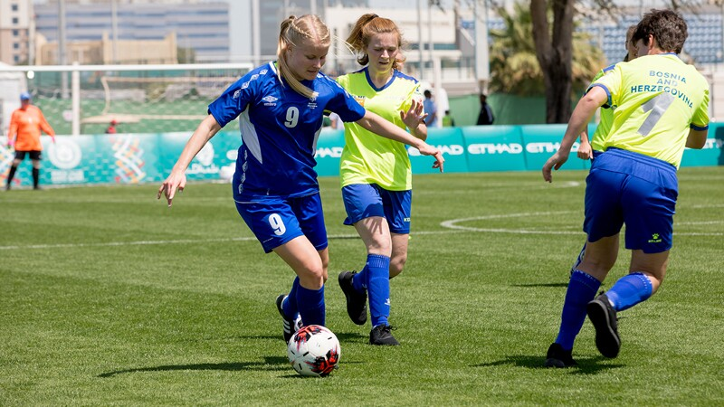 Three female footballers on the field. One girl is dribbling the ball as to opponents approach her.