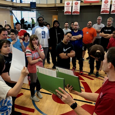 Female Health Messenger shows teaching aid documents to a group of athletes in a gymnasium.