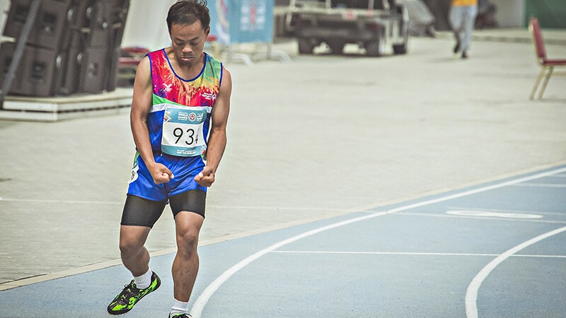 Nakorn running on the track during an athletes competition. He has on a brightly colored tank top, blue shorts, and black spandex.